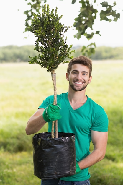 Gelukkige jonge mens die voor de gemeenschap tuiniert Premium Foto