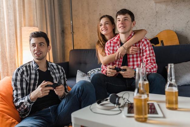 Gelukkige jonge mensen die videogames spelen, plezier hebben, vrienden feest thuis, close-up handen met joystick, hipster bedrijf samen, glimlachen, positief, lachen, competitie, bierflesjes op tafel Gratis Foto