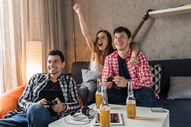 Gelukkige jonge mensen die videogames spelen, plezier hebben, vriendenfeestje thuis, hipster gezelschap samen, twee mannen één vrouw, glimlachen, positief, ontspannen, emotioneel, lachen, competitie Gratis Foto