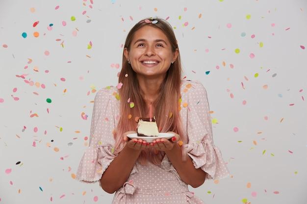 Gelukkige jonge mooie dame met lichtbruin lang haar die vrolijk opzij kijkt terwijl ze de verjaardagstaart in haar handen houdt, een wens doet en zich verheugt over een leuk feestje, geïsoleerd over witte muur Gratis Foto