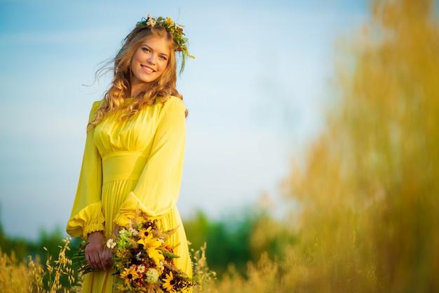 Gelukkige jonge mooie vrouw die bloemslinger op gebieden met enorme zonlichtgloed draagt Premium Foto