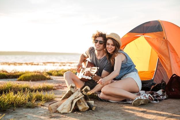 Gelukkige jonge paar gitaarspelen en marshmallows samen op vreugdevuur bakken Premium Foto
