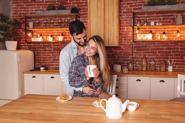Gelukkige jonge paar het drinken thee bij de keuken Gratis Foto