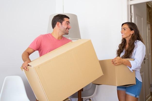 Gelukkige jonge paar verhuizen naar nieuw appartement, met kartonnen dozen, rondkijken en glimlachen Gratis Foto