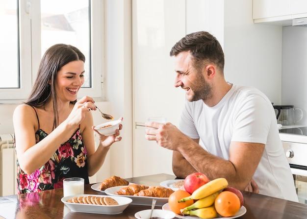 Gelukkige jonge paarzitting in keuken die ontbijt heeft Premium Foto