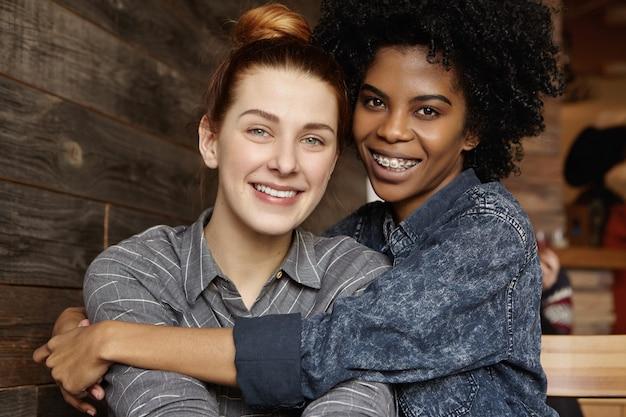 Gelukkige jonge sex tussen verschillendre rassen homoseksueel paar leuke tijd samen doorbrengen bij moderne coffeeshop Gratis Foto