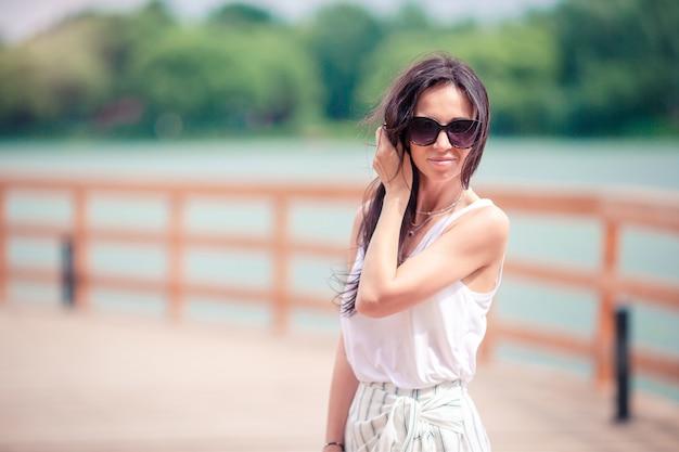 Gelukkige jonge stedelijke vrouw het drinken koffie in europese stad. Premium Foto