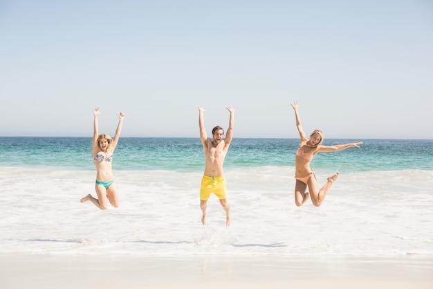 Gelukkige jonge vrienden die op het strand springen Premium Foto