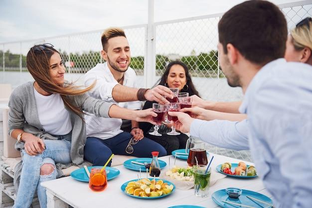 Gelukkige jonge vrienden zaten aan een tafel en hadden een picknick buiten. Gratis Foto