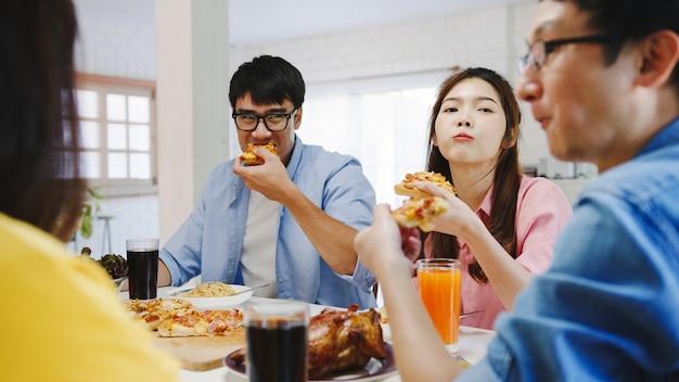 Gelukkige jonge vriendengroep die thuis lunch heeft. azië familiefeest pizza eten en lachen genieten van maaltijd zittend aan de eettafel samen thuis. viering vakantie en saamhorigheid. Gratis Foto