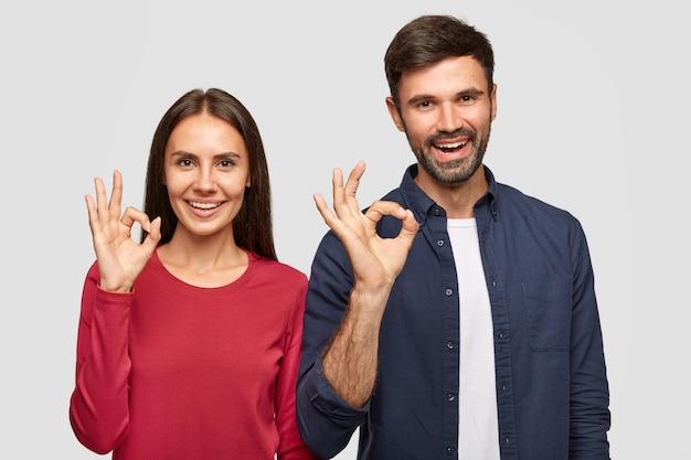 Gelukkige jonge vriendin en vriendje tonen ok teken met handen, drukken uitstekend symbool uit, tonen hun goedkeuring of instemming, hebben vrolijke uitdrukkingen, staan binnen tegen witte muur Gratis Foto