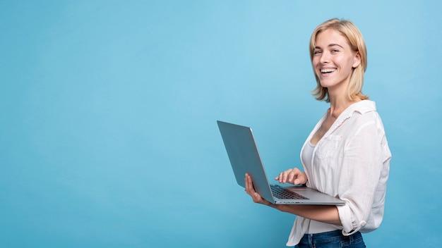 Gelukkige jonge vrouw die een notitieboekje houdt Gratis Foto
