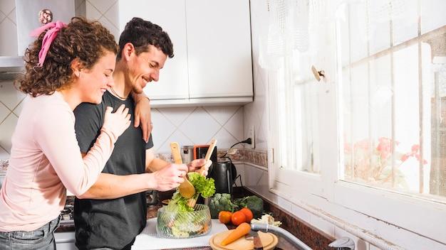 Gelukkige jonge vrouw die haar echtgenoot van achter het voorbereidingen treffen van salade in de kom omhelzen Gratis Foto