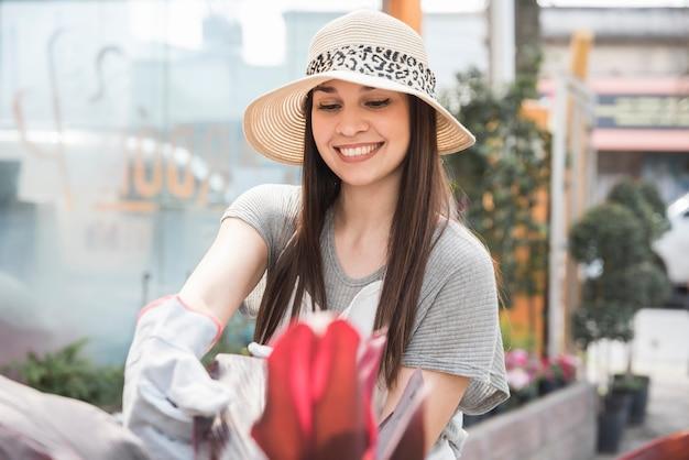 Gelukkige jonge vrouw die hoed draagt die auto van installatie neemt Gratis Foto