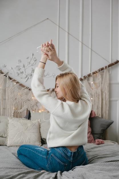 Gelukkige jonge vrouw die in hoofdtelefoons aan muziek van smartphone luisteren en thuis op bed dansen Premium Foto