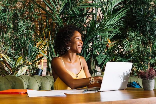 Gelukkige jonge vrouw die laptop met documenten en digitale tablet op houten lijst met behulp van Gratis Foto