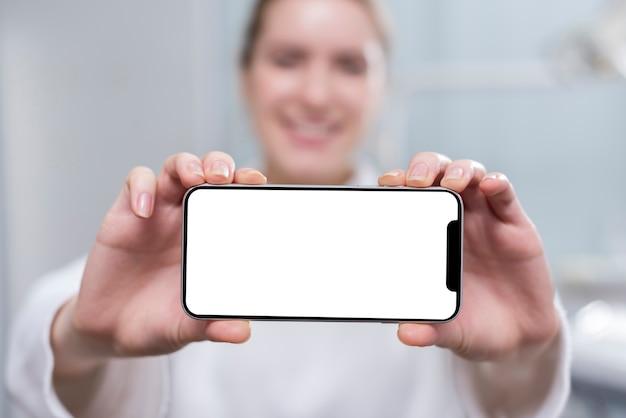 Gelukkige jonge vrouw die mobiele telefoon houdt Gratis Foto
