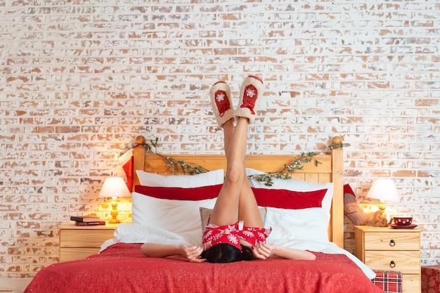 Gelukkige jonge vrouw die op het bed met opgeheven omhoog benen ligt Gratis Foto