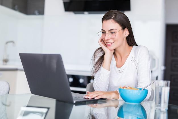 Gelukkige jonge vrouw die salade van een kom eten en jus d'orange drinken terwijl status op een keuken en het letten van op film op laptop Gratis Foto