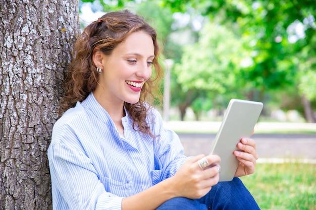 Gelukkige jonge vrouw die via telecommunicatie app op tablet spreekt Gratis Foto