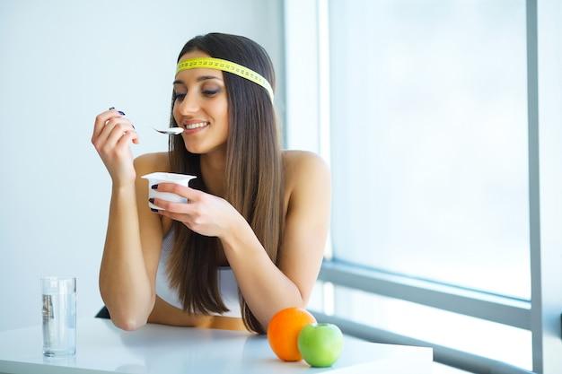 Gelukkige jonge vrouw die yoghurt in keuken eet Premium Foto