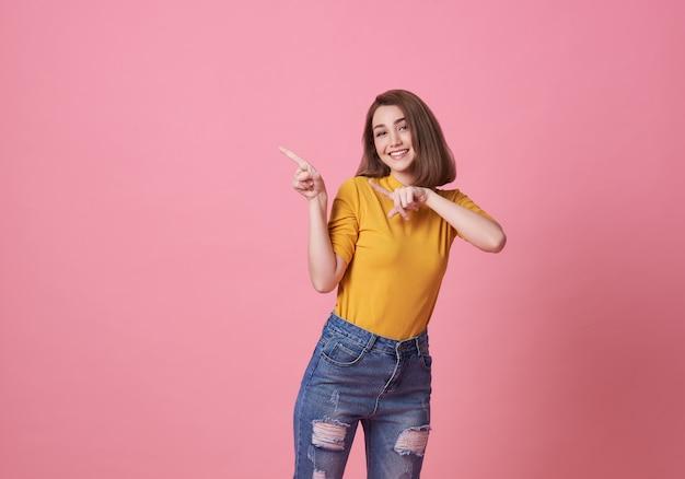 Gelukkige jonge vrouw die zich met haar vinger bevindt die over roze banner met exemplaarruimte richt. Premium Foto