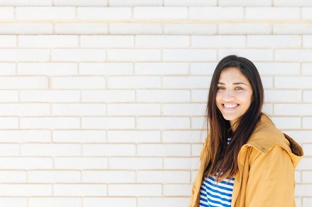 Gelukkige jonge vrouw die zich tegen bakstenen muur bevindt Gratis Foto