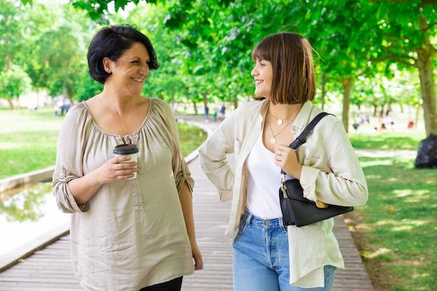 Gelukkige jonge vrouw en haar moeder die en in park babbelen lopen Gratis Foto