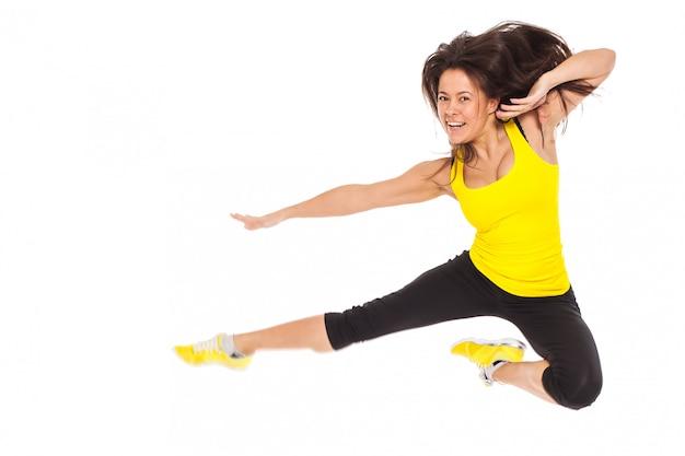 Gelukkige jonge vrouw in fitness slijtage sprongen Gratis Foto