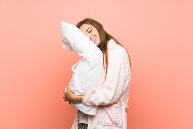 Gelukkige jonge vrouw in peignoir over roze muur Premium Foto