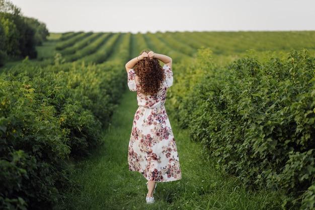 Gelukkige jonge vrouw met bruin krullend haar, dat een kleding draagt, die in openlucht in een tuin stelt Gratis Foto