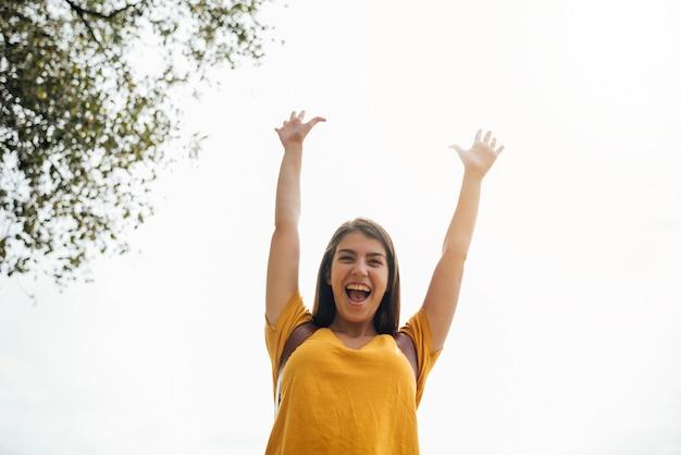 Gelukkige jonge vrouw met haar handen omhoog lage hoekmening Gratis Foto