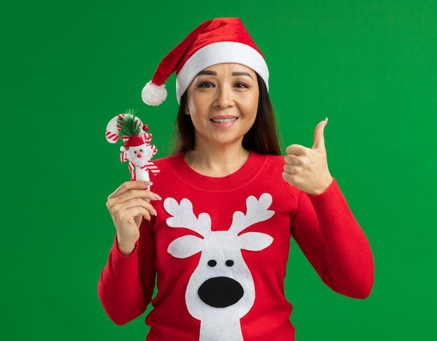Gelukkige jonge vrouw met kerst kerstmuts en rode trui bedrijf kerst candy cane kijken camera glimlachen tonen thumbs up staande over groene achtergrond Gratis Foto