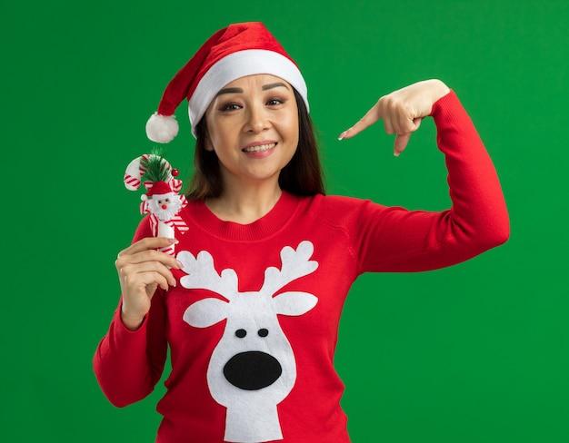 Gelukkige jonge vrouw met kerst kerstmuts en rode trui met kerst candy cane wijzend met wijsvinger naar het glimlachend staande over groene achtergrond Gratis Foto
