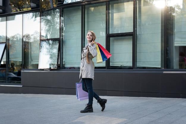 Gelukkige jonge vrouw met kleurrijke zakken dichtbij wandelgalerij. Premium Foto