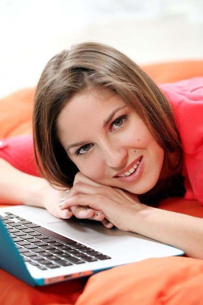 Gelukkige jonge vrouw met laptop Gratis Foto
