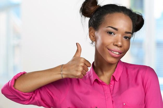 Gelukkige jonge vrouw met omhoog duimen Premium Foto