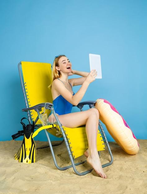 Gelukkige jonge vrouw met tablet neemt selfie of vlog over reizen op blauwe studioachtergrond. concept van menselijke emoties, gezichtsuitdrukking, zomervakantie, weekend. zomer, zee, oceaan, alcohol. Gratis Foto