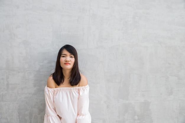 Gelukkige jonge vrouw tegen concrete muur. Premium Foto
