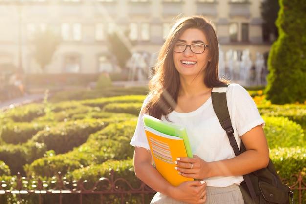 Gelukkige jonge vrouwelijke student met boeken in de handen op de universitaire achtergrond. Premium Foto
