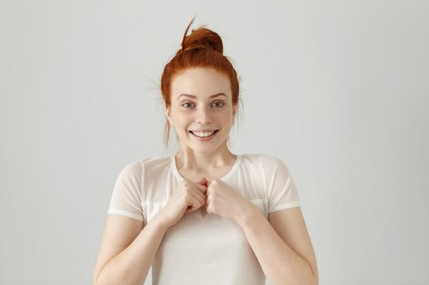 Gelukkige jonge vrouwelijke werknemer die zich over haar succes op het werk verheugt, breed glimlachend en gebalde vuisten houdt. mooi roodharig meisje in blouse gevoel blij en opgewonden Gratis Foto
