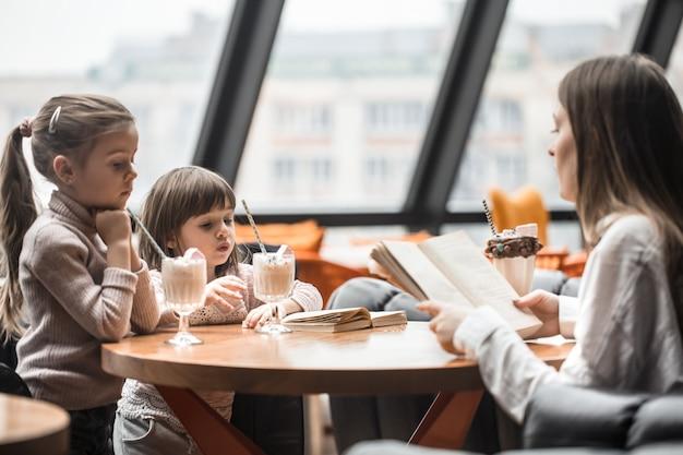 Gelukkige jonge vrouwenmoeder met kinderen die bij dinerlijst zitten en in restaurant spreken Premium Foto