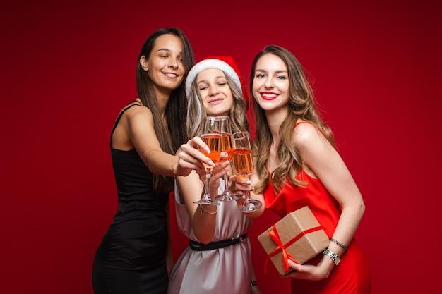 Gelukkige jonge vrouwenvrienden met gift en champagne die vakantie samen vieren op partij op rode achtergrond, exemplaarruimte Gratis Foto
