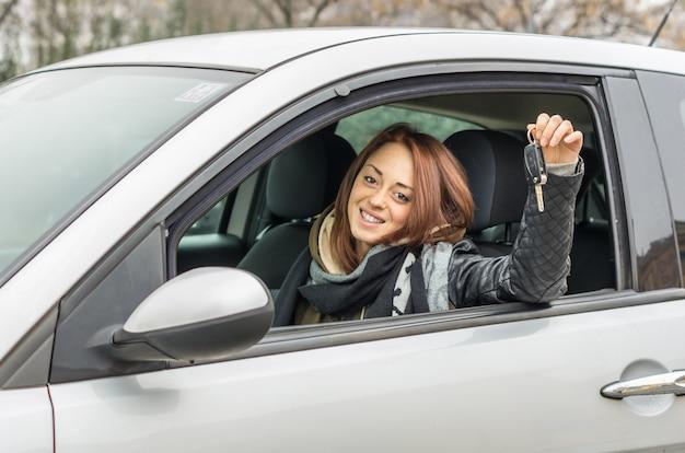 Gelukkige jonge vrouwenzitting in auto het glimlachen Premium Foto