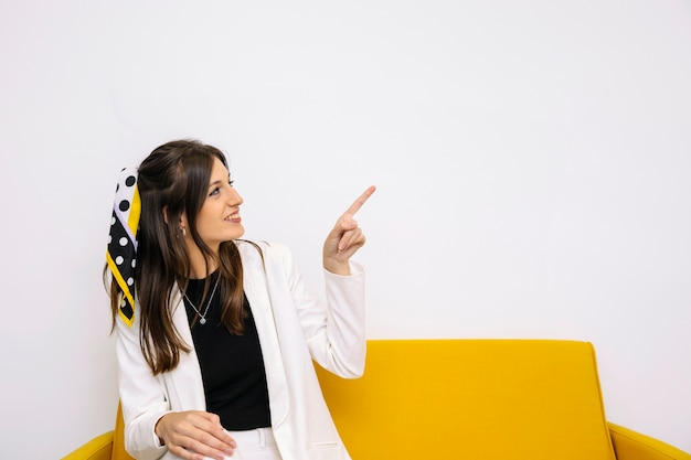 Gelukkige jonge vrouwenzitting op gele bank die stijgend benadrukt Gratis Foto