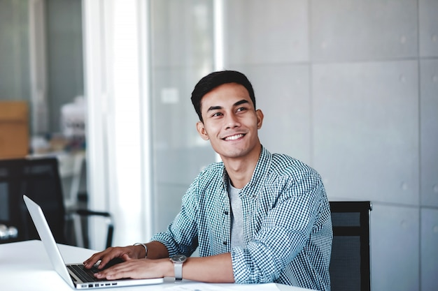 Gelukkige jonge zakenman die aan computerlaptop werkt in bureau. glimlachend en wegkijken Premium Foto