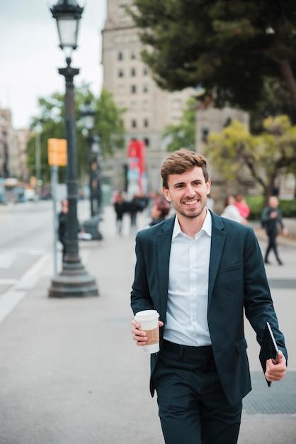 Gelukkige jonge zakenman die op straat met zijn digitale tablet en beschikbare koffiekop lopen Gratis Foto