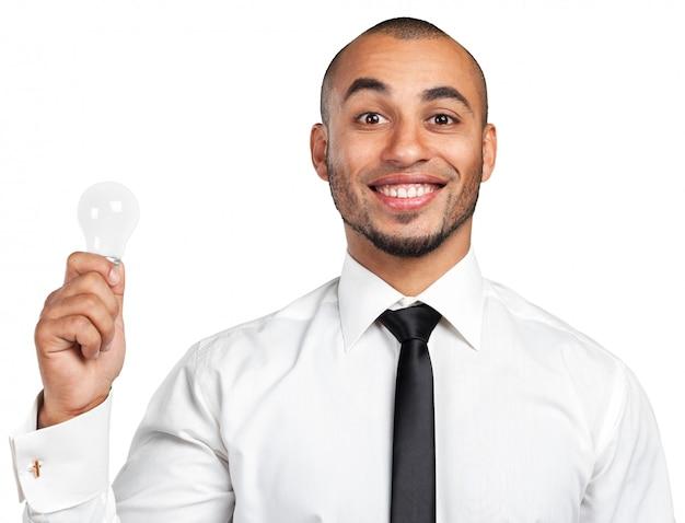 Gelukkige jonge zakenman holding light bulb Premium Foto