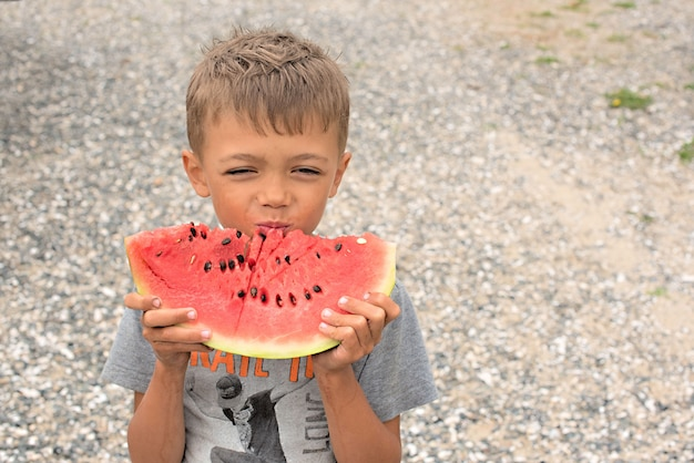 Gelukkige jongen die een rijpe watermeloen eet. Premium Foto