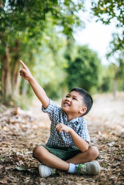 Gelukkige jongen die en alleen in het park zitten denken Gratis Foto